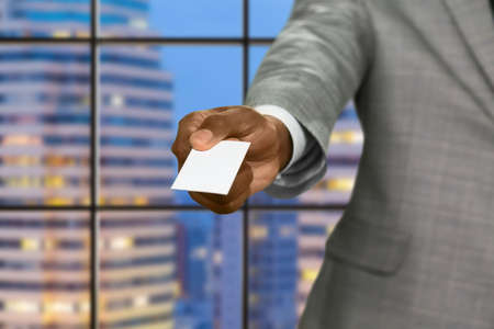 megalopolis: Afro businessman gives visit card. Blank card on megalopolis background. Realtor in capital city. Place for your advertising. Stock Photo