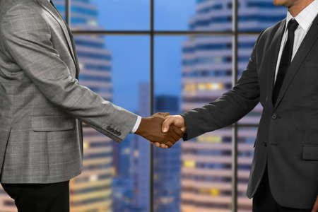 megalopolis: Adult businessmen shake hands. Greeting of men in megalopolis. Pacified by rules of etiquette. Topmanagers at the meeting.