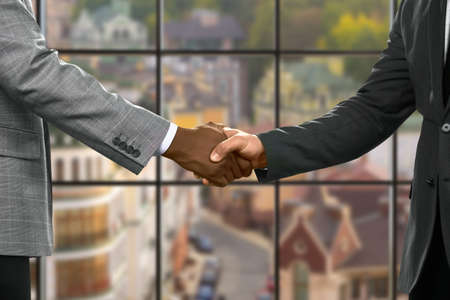 appreciating: Formally dressed men shaking hands. Officials shake hands at midday. Appreciating the support. Always ready to help.