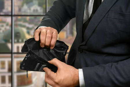 truly: Empty wallet in businessmans hands. Empty wallet on urban background. Waiting for salary. Truly sad situation. Stock Photo
