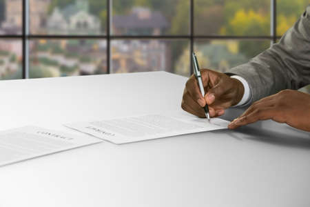 Black businessmans hand signs contract. Man signing contract at daytime. Opportunity to get great job. Safety is guaranteed. Stock Photo