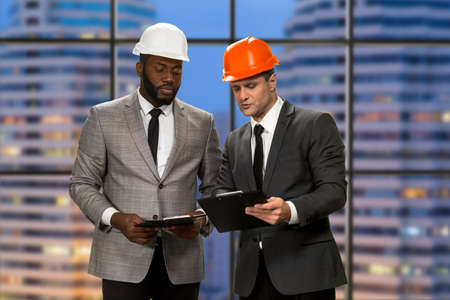Businessmen in helmets holding clipboards. Construction managers near skyscraper. Re-building an entire district. This is way too expensive. Stock Photo