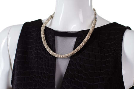 inset: Black top with simple necklace. Plain bijouterie necklace on mannequin. Dark top with net inset. Exclusive element of womans apparel.
