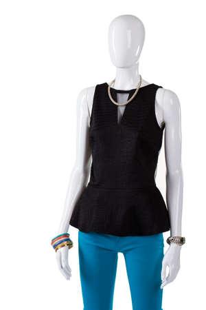 Dark top with turquoise pants. Black v-neck top on mannequin. Trendy black top and trousers. Marked down clothing on display.