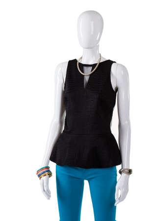 pantalones abajo: superior oscuro con pantalones de color turquesa. Top negro con cuello en V en maniquí. De moda top negro y pantalón. Marcado por la ropa en la pantalla. Foto de archivo