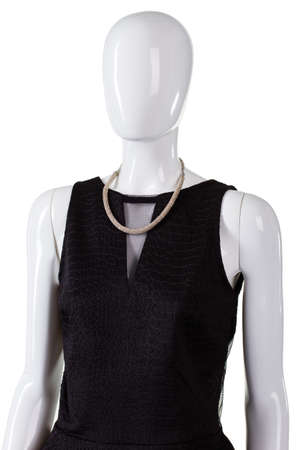 inset: Black sleeveless top and necklace. Metal necklace on female mannequin. Neckline with net inset. Fashionable dark top on sale.