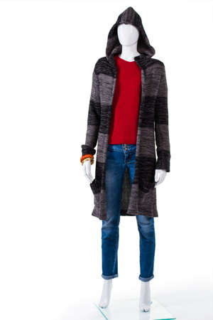 outerwear: Striped sweater coat with hood. Female mannequin in sweater coat. Ladys soft outerwear on display. Clothes for dry cool weather. Stock Photo