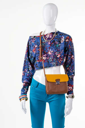 outlet store: Floral crop top and purse. Stylish bicolor bag on mannequin. Girls outfit with leather handbag. Accessory sale in outlet store.