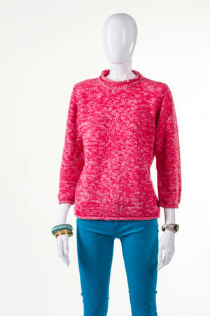 womans clothing: Turquoise pants and pink sweatshirt. Mannequin wearing pink woolen sweater. Womans bright spring clothing. Handmade pullover sold at discount.