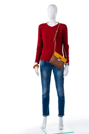 skinny jeans: Skinny jeans and red sweater. Mannequin wearing pullover with jeans. Idea for womans autumn outfit. Trendy clothing in local boutique.