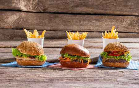 high calorie: Hamburgers and cups with fries. Table with burgers and fries. Delicious high calorie meal. Taste you will never forget.