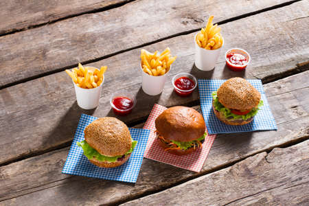 freshly cooked: Hamburgers and fries with ketchup. Table with fast food meal. Freshly cooked junk food menu. High-calorie food in cafe. Stock Photo