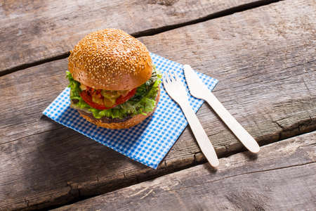 Burger with paper cutlery. Fresh hamburger on old table. Traditional burger with sesame bun. Hearty breakfast in local cafe. Stock Photo