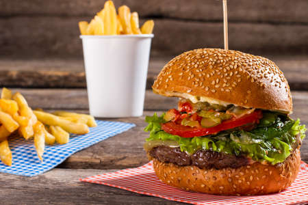 well made: French fries and big burger. Junk food on brown table. Well made burger in cafe. Example of popular junk food. Stock Photo