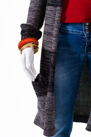 low prices: Sweater coat and gold bracelet. Mannequin in outerwear with bracelets. Womans outfit and wrist accessories. Low prices for new merchandise.