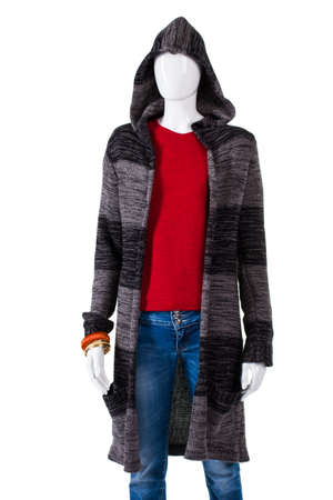 outerwear: Striped hooded sweater coat. Mannequin in outerwear and jeans. Trendy autumn apparel on showcase. Ladys dark-colored outerwear. Stock Photo