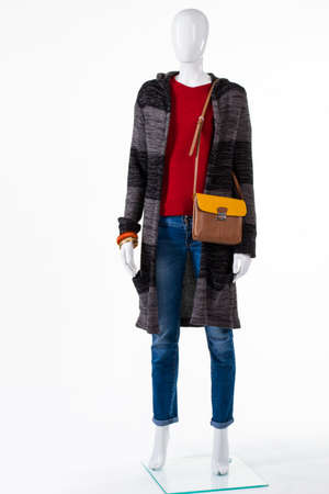 outerwear: Sweater coat and bicolor purse. Mannequin in outerwear with bag. Brown and yellow leather handbag. Accessory choice for autumn outfit.