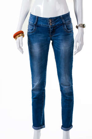 skinny jeans: Skinny jeans and wrist accessories. Mannequin wearing jeans with bracelets. Casual blue pants on display. Discounts for denim clothing. Stock Photo