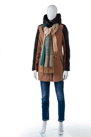 outerwear: Jacket with jeans and scarf. Female mannequin wearing brown jacket. Ladys autumn outerwear with scarf. Fashionable and warm clothing.