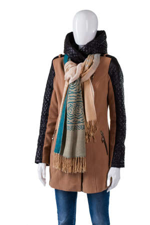 outerwear: Long brown jacket with scarf. Mannequin wearing jacket with inserts. Leather inserts on sleeves. Womans trendy outerwear from magazine. Stock Photo