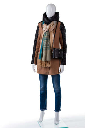outlet store: Brown jacket and black bag. Mannequin wearing jacket with purse. Ladys outerwear with classic handbag. Clothes selection in outlet store.