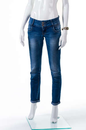 womans clothing: Ladys skinny fit jeans. Blue jeans on female mannequin. Plain blue jeans and watch. Seasonal discount for womans clothing. Stock Photo