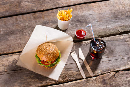 norm: Hamburger with cola and fries. Cola glass and burger. Fast food and tomato sauce. Your daily calorie norm.