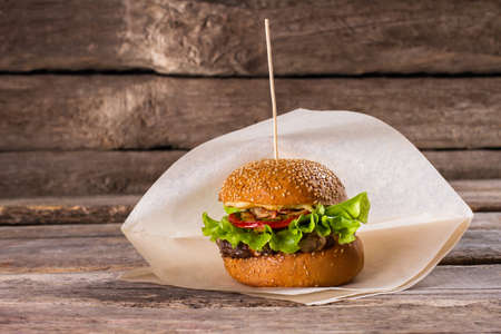 beefburger: Fresh burger on a stick. Beefburger on wooden background. Juicy beef and fresh vegetables. Well-made burger in bistro.