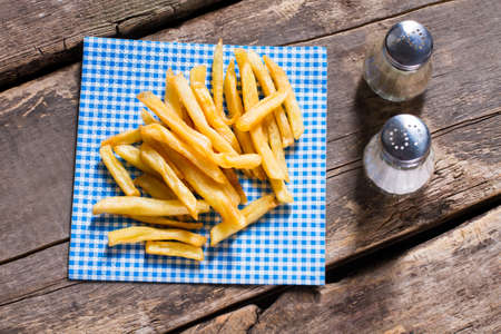 pepperbox: Fries on napkin and pepperbox. Table with spices and fries. Fries at fast food restaurant. Simple old recipe.