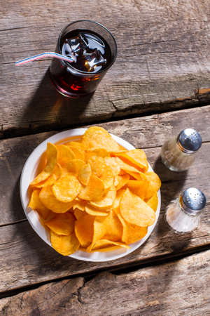 pepperbox: Chips with cola and pepperbox. Cola and chips on table. Portion of chips with beverage. Salty snack and cool drink.