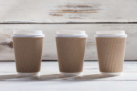 lids: Ripple cups with lids. Three ripple paper cups. White wooden table with cups. Different grades of coffee. Stock Photo