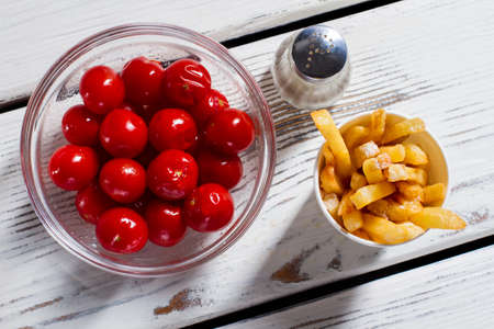pepperbox: Tomatoes, fries and pepperbox. French fries with red tomatoes. Breakfast snack on white table. Vitamins and energy.