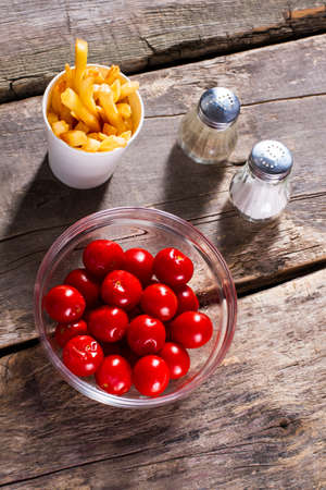 processed food: Tomatoes and fries with salt. Pepper and tomatoes on table. Processed food and fresh vegetables. Make your choice. Stock Photo