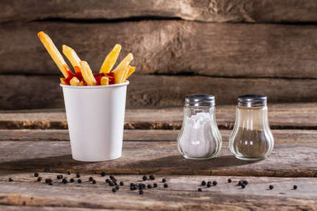 pepperbox: Cup of fries with pepperbox. Salt, pepperbox and fries. Fast food snack on table. So fresh and crispy.