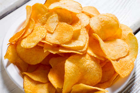 processed food: Potato chips on a plate. White plate with yellow chips. Fast snack at new diner. Good example of processed food. Stock Photo