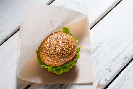 beefburger: Big burger on a stick. Burger laying on paper wrap. Beefburger for breakfast. Well-made dish in bistro.