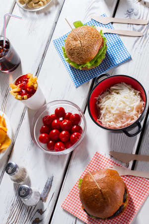 pepperbox: Burgers, pepperbox and tomatoes. Sauerkraut with burgers and cutlery. Lunch on white wooden table. Many shades of taste.