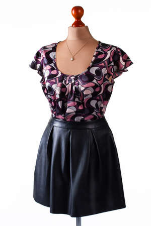 leather skirt: Casual blouse and black skirt. Skirt and blouse on mannequin. Leather skirt with stylish top. Girls casual outfit and accessory.