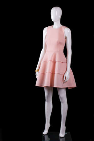 Sleeveless salmon dress with folds. Salmon dress on white mannequin. Stylish mannequin on black background. Trendy garment with golden accessory. Stock Photo