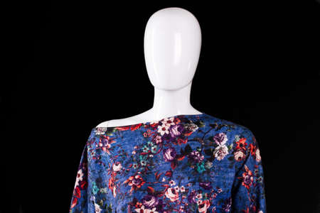 woman's clothing: Asymmetric top with floral pattern. Blue top on white mannequin. Womans fashionable summer top. Trendy clothing made of cotton.
