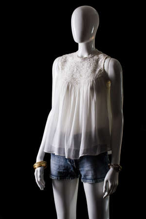 sleeveless top: White sleeveless top and shorts. Shorts and top on mannequin. Womans fashionable summer outfit. Simplicity and beauty.