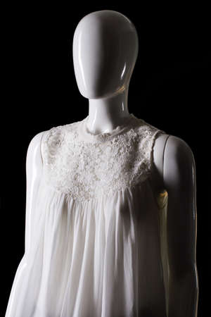 sleeveless top: Sleeveless white top with insert. Mannequin in white sleeveless top. Seasonal offer at fashion store. Quality merchandise at fair price. Stock Photo
