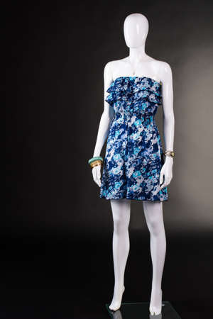 strapless: Short blue dress without straps. Strapless floral dress on mannequin. Summer clothing on black background. Womans vintage style garment.