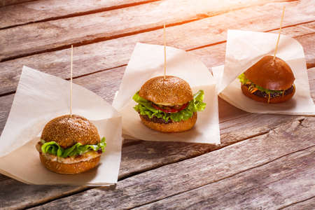 wrappers: Hamburgers on white wrappers. Old wooden table with burgers. Juicy lettuce and warm buns. Savoury burgers in local bistro. Stock Photo