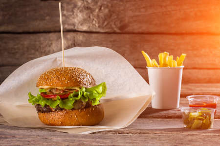 beefburger: Burger on paper and fries. Table with beefburger and fries. Sliced pickles and fast food. High-calorie lunch at restaurant.