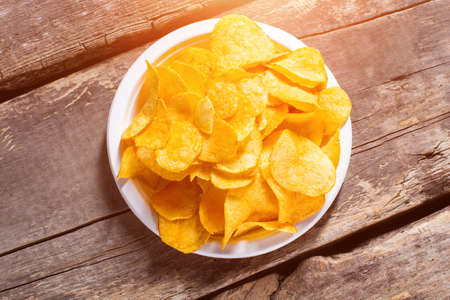 processed food: Potato chips pile on plate. Chips on brown wooden background. Fast snack at the diner. Example of processed food.