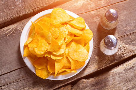 pepperbox: Chips with salt and pepperbox. Pepperbox and chips on table. Simple recipe of potato chips. Popular junk food and spices.