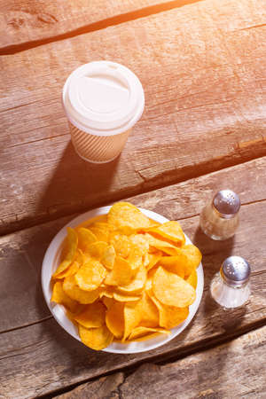 pepperbox: Chips and hot drink cup. Drink and chips on table. Hot coffee and crispy food. Morning snack in retro cafe. Stock Photo