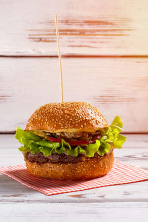 beefburger: Burger on wooden stick. Big burger laying on napkin. White table with fresh beefburger. Fat and calories.