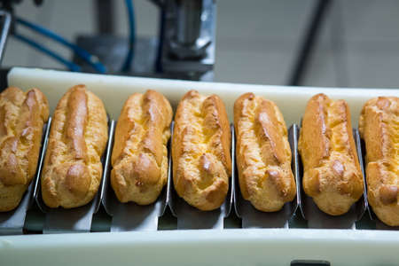 filling line: Conveyor line with eclairs. Baked pastry laying on conveyor. Dessert with cream filling. Crispy food produced at factory. Stock Photo